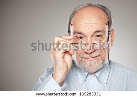 Portrait of old man taking glasses / Man in studio looking at camera - stock photo