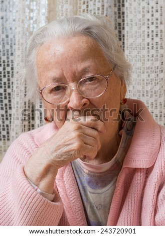 Portrait of old sad woman in glasses at home