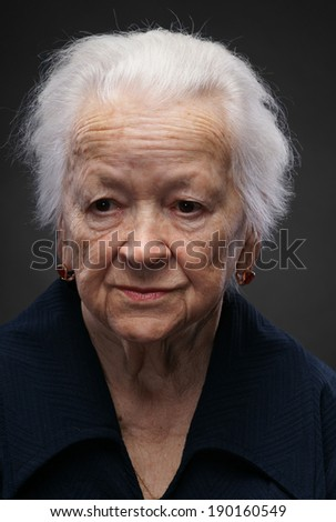 Portrait of old sad woman on a gray background