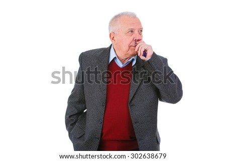 Portrait of old senior business man dressed in suit, shirt and marsala cardigan, wipes nose into a tissue with a cold, flu or allergy, isolated on white background. facial expressions - stock photo