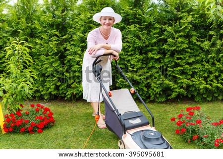 Portrait of Old senior woman gardener 65 years old in hat with an electric mower in garden, summer morning.