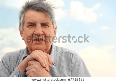 portrait of old serious senior in striped shirt, chin on hands, looking at camera, sky