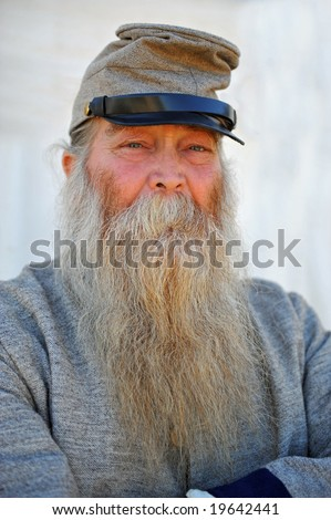 Portrait of old soldier in confederate uniform wearing long white beard - stock photo