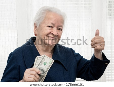 Portrait of old woman holding money in hands - stock photo