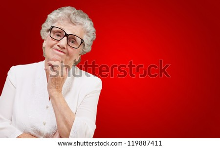 Portrait Of Old Woman On Red Background - stock photo