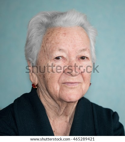Portrait of old woman posing at home