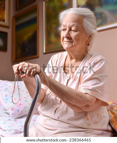Portrait of old woman sitting with a cane - stock photo