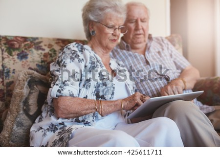 Portrait of old woman sitting with her husband and using digital tablet. Senior couple sitting on sofa at home with a touch screen computer. - stock photo