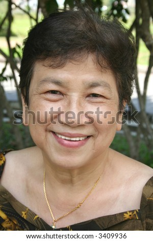 Portrait of old woman smiling in the park - stock photo