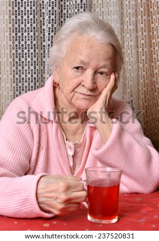 Portrait of old woman with cup of tea at home