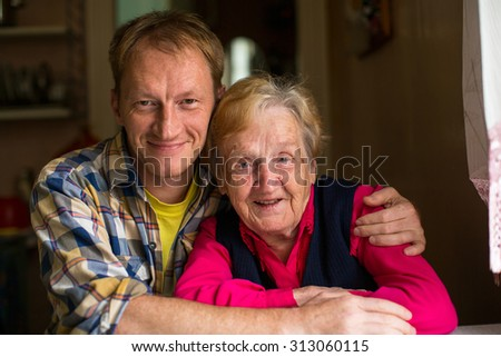 Portrait of old woman with his adult grandson. - stock photo