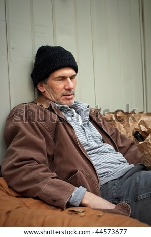 Portrait of older homeless man sleeping outdoors, leaning against a building, surrounded by his sleeping bag, wine bottle in paper sack, etc.