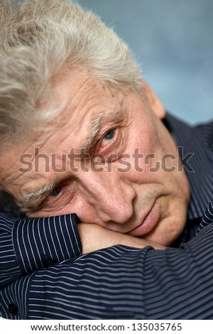 portrait of older man in a shirt over  gray background