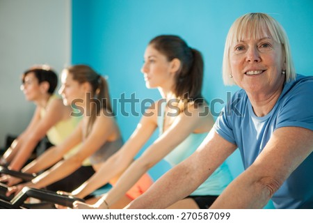 Portrait of older woman looking towards the camera while cycling - stock photo