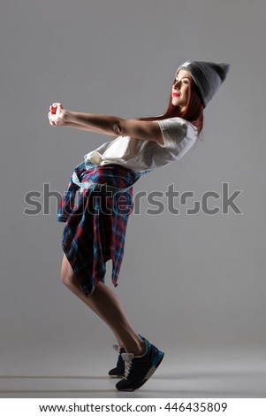 Portrait of one attractive cheerful fit cute hipster young woman wearing casual clothing and beanie dancing. Modern style beautiful dancer girl warming up. Full length image, studio gray background - stock photo