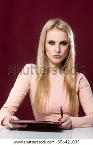 Portrait of one attractive elegant sensual serious young blonde business woman with long hair in pink dress sitting at white table holding brown folder and pen looking forward, vertical picture