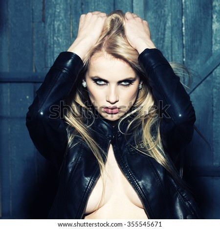 Portrait of one attractive sensual sexy young serious passionate blonde woman touching long hair with hands in leather black jacket in studio on wooden wall background, square picture