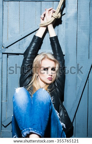 Portrait of one attractive sensual sexy young serious passionate blonde woman with long hair in leather black jacket and jeans with raised hands in rope on wooden background, vertical picture