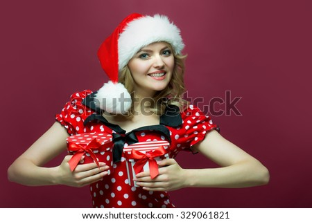 Portrait of one beautiful funny young new year woman with blond curly hair in dress and red santa claus hat with two wrapped gift boxes for christmas standing in studio on purple background, vertical - stock photo