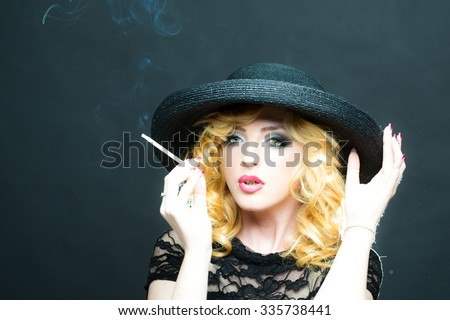 Portrait of one beautiful sensual sexy young retro blonde woman with curly hair and red lips in round black hat looking forward smoking cigarette on studio background, horizontal picture - stock photo