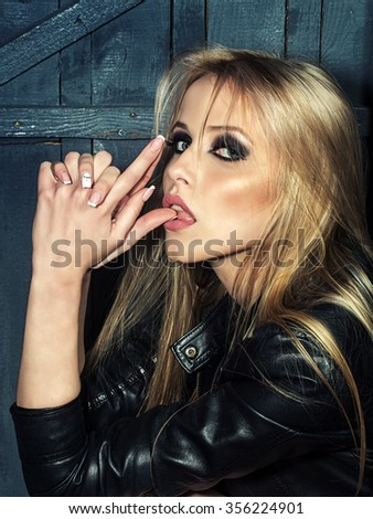 Portrait of one beautiful sensual sexy young serious passionate blonde woman with long hair in leather black jacket holding hands as gun in studio on wooden wall background, vertical picture - stock photo