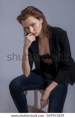 Portrait of one beautiful young slim woman with white skin and brown hair in black jacket, dark blue jeans and black underwear bra sitting on gray background