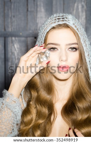 Portrait of one enchanted enigmatic beautiful sensual young woman with long lush curly hair in blue knitted cloth holding big magic white faceted stone precious gem as elixir of youth and beauty - stock photo
