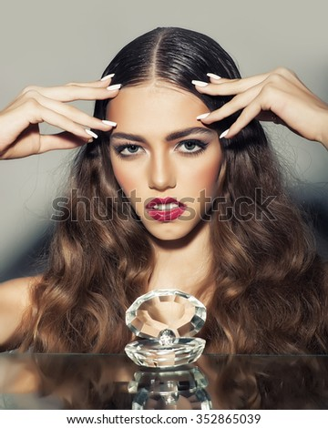 Portrait of one glamour fashionable sensual pretty young stylish woman with beautiful curly long hair and bright red lips and makeup with luxurious glassy decorative shell with pearl, vertical picture - stock photo