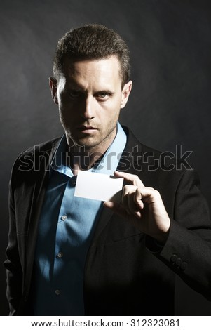 Portrait of one handsome sexual unshaven young business man in jacket and blue shirt holding white visiting card in hand looking forward standing on black studio background copyspace, vertical picture - stock photo