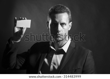 Portrait of one handsome sexy unshaven young man in jacket and shirt holding business card in hand looking forward standing on studio background black and white copyspace, horizontal picture - stock photo