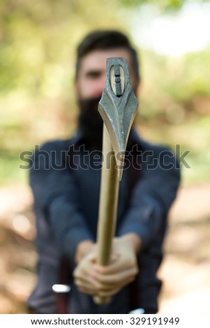 Portrait of one handsome strong stylish male logger of young serious man with long lush black beard and moustache in shirt holding wooden axe standing sunny day outdoor on natural background, vertical - stock photo