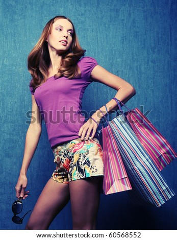 portrait of one happy young adult girl with colored bags - stock photo