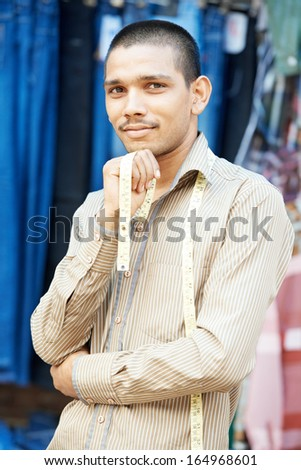 Portrait of one Indian tailor trade seller man with measure tape outdoors - stock photo