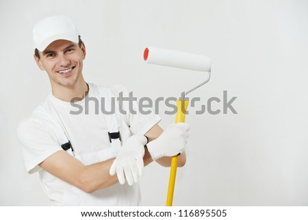 Portrait of one male house painter worker with painting roller - stock photo