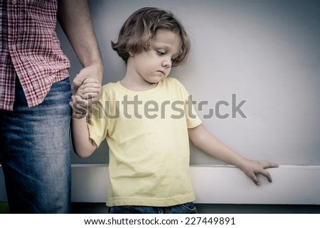 portrait of one sad son hugging his father at the day time - stock photo