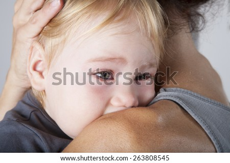portrait of one year age blonde lovely cute caucasian white baby grey shirt looking  face crying and scream shout with tears eyes in brunette woman mother arms embrace hug - stock photo