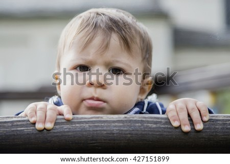 Portrait of one year old baby looking at camera seriously while holding hands on wooden fence
