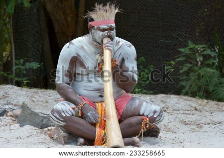 Portrait of one Yugambeh Aboriginal man play Aboriginal  music on didgeridoo, instrument during Aboriginal culture show in Queensland, Australia. - stock photo