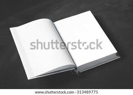 portrait of open thick book with blank page on black board for background - stock photo