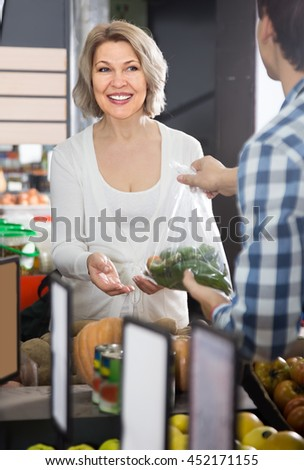Portrait of ordinary mature woman buying green pepper in grocery and smiling