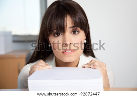 Portrait of overstrained woman at her desk with pile of paperwork - stock photo