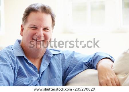 Portrait Of Overweight Man Sitting On Sofa - stock photo