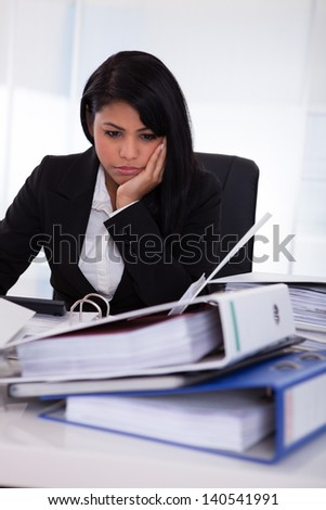 Portrait Of Overworked Businesswoman Looking At Folder - stock photo