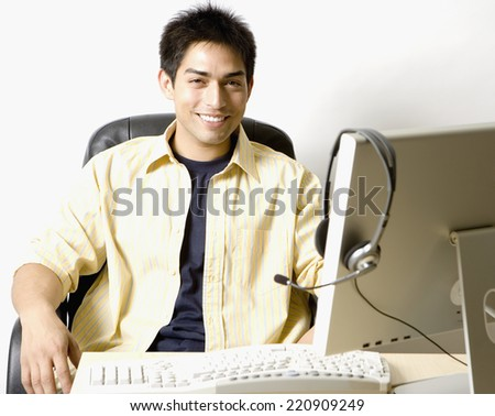 Portrait of Pacific Islander businessman at desk - stock photo