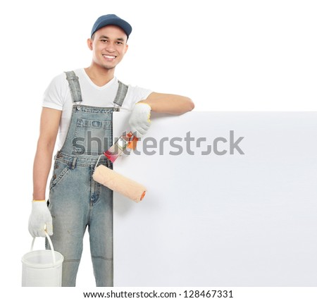 portrait of paint worker with tool hold a big blank white banner - stock photo