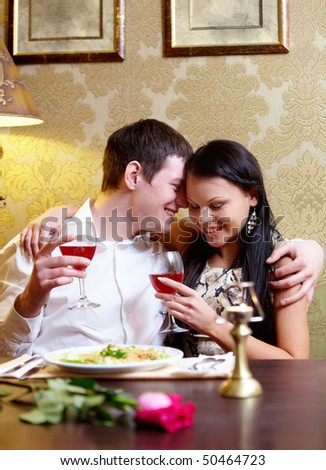 Portrait of pair of lovers holding glasses during lunch - stock photo
