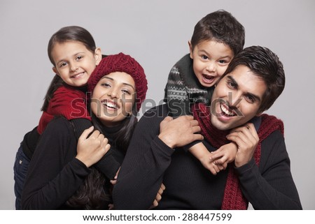 Portrait of parents and children over grey background - stock photo