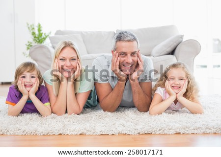Portrait of parents and children with head in hands lying on rug at home - stock photo
