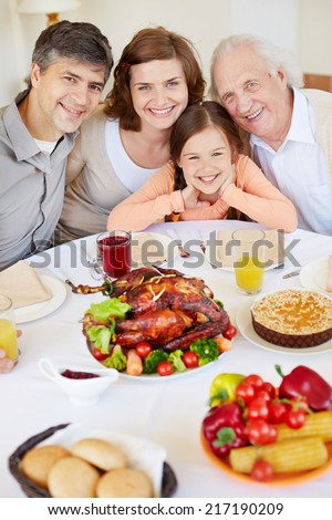Portrait of parents, their daughter and senior man sitting at festive table and looking at camera