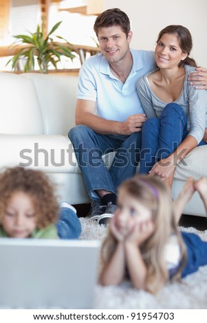 Portrait of parents watching their children using a laptop in their living room - stock photo